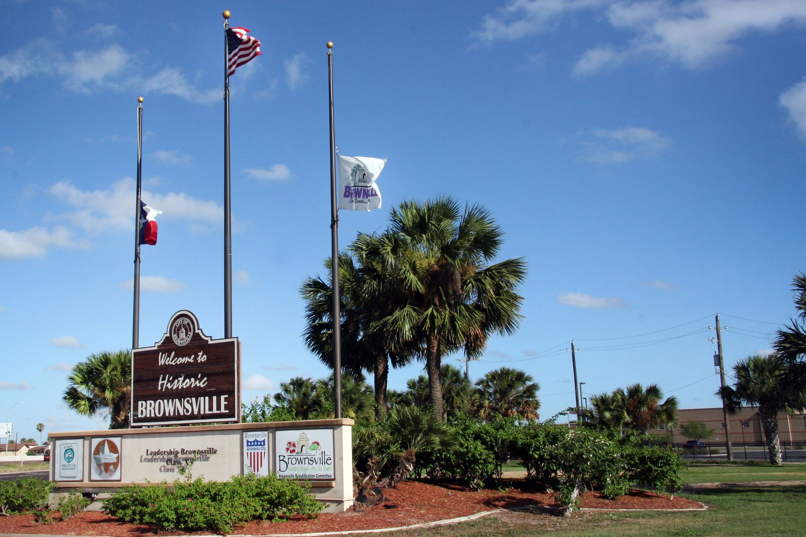 The Welcome to Brownsville sign with three flags and trees behind it.