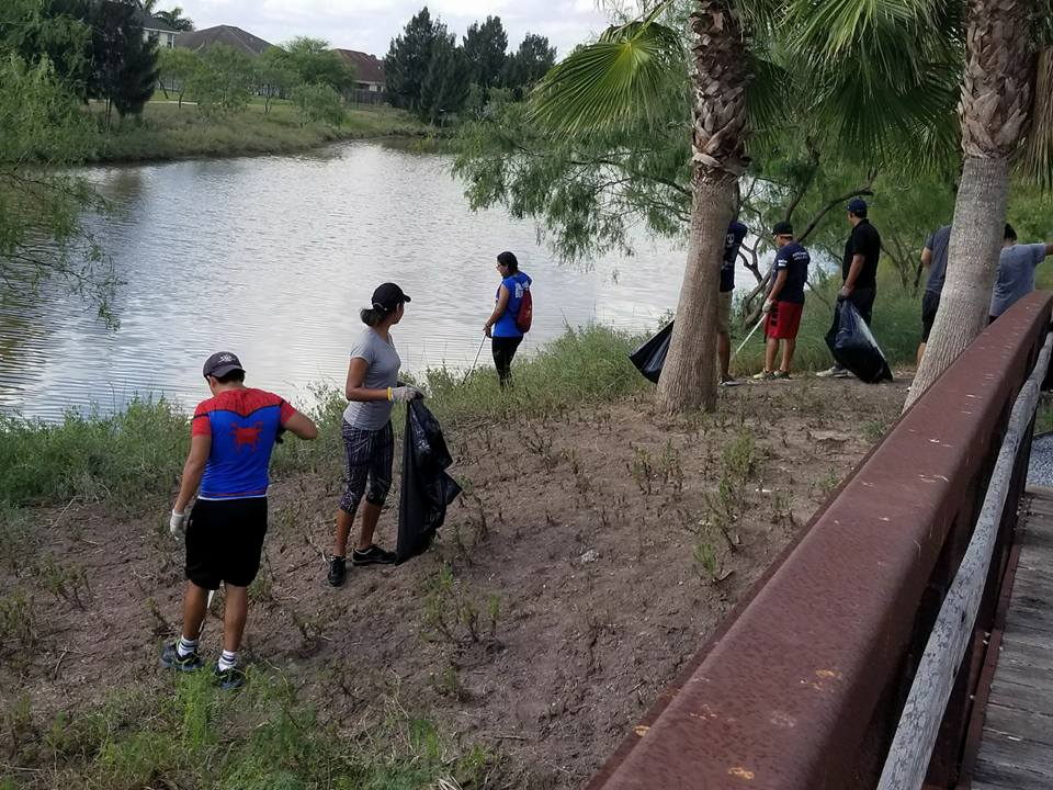 Volunteers in a group picking up trash at park clean up